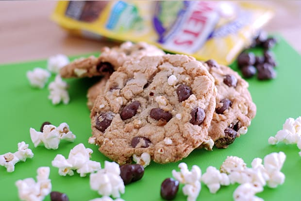 Cookies with raisinets and popcorn, on a green paper. Raisinet wrappers in the background and popcorn and loose raisinets in the foreground.