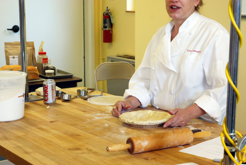 King Arthur Flour employee Robyn demonstrates tucking pie crust edges under in order to make prettier edges. Taken at the King Arthur Flour Baking Education Center.
