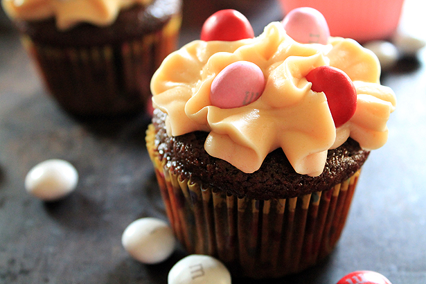 A chocolate cupcake with peanut butter frosting and pink, red, and white M&Ms. The batter is made with Shiner Bock beer.