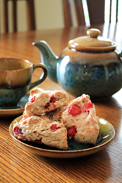 Three strawberry scones sit on a plate. A blue teapot and cup sit in the background.