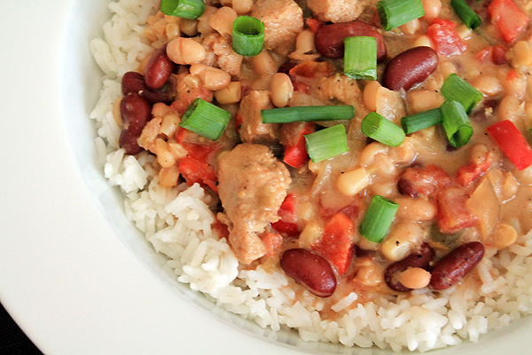 White chicken chili in a bowl, over rice. The chili includes chicken breast, kidney beans, navy beans and white shoepeg corn.