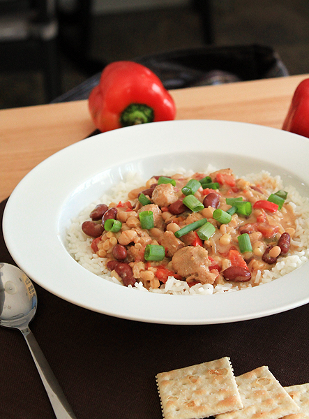 White chicken chili in a bowl, surrounded by saltine crackers and red peppers. The chili is served over white rice.