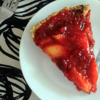 Peach Raspberry refrigerator pie on a white plate. Two forks sit nearby on a cloth napkin.