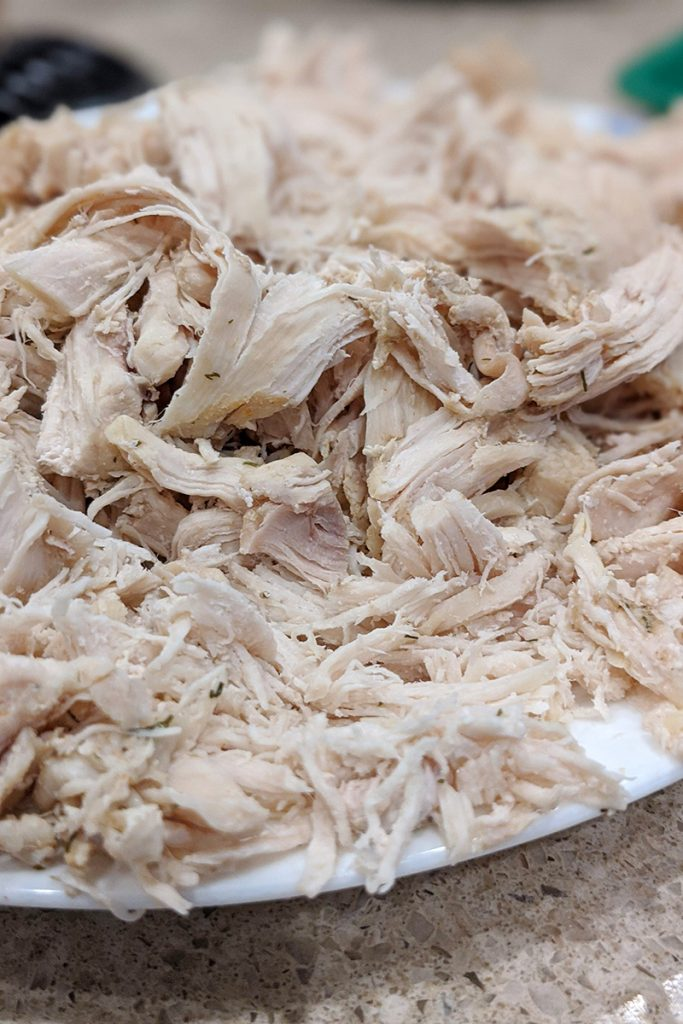 Pulled chicken strands on a white plate. This will be added to a broth with carrots as the base for Chicken and Dumplings.